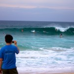 boy photographs surfers at Pipeline